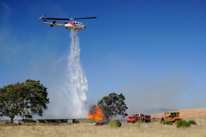 helicopter dumps water on a grass fire